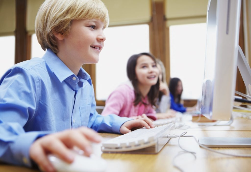Young boy using computer in classroom with students in background